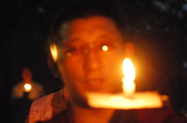 A Tibetan monk holds a candle light to protest Chinese rule over Tibet. Photo: TPI/file