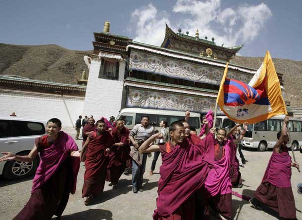 Tibetan Monks carry their national flag and shout slogans as a group of journalists, invited to an official visit by the local government, arrived at the Labrang Monestry, eastern Tibet, April 9, 2008. Photo: TPI