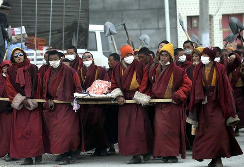 Tibetan monks carry the body of a quake victim during a funeral procession in Kyigudo (Yushu ) county, eastern Tibet, Tso-Ngon Region (Ch: province of Qinghai) on April 21, 2010. Photo: Getty Images