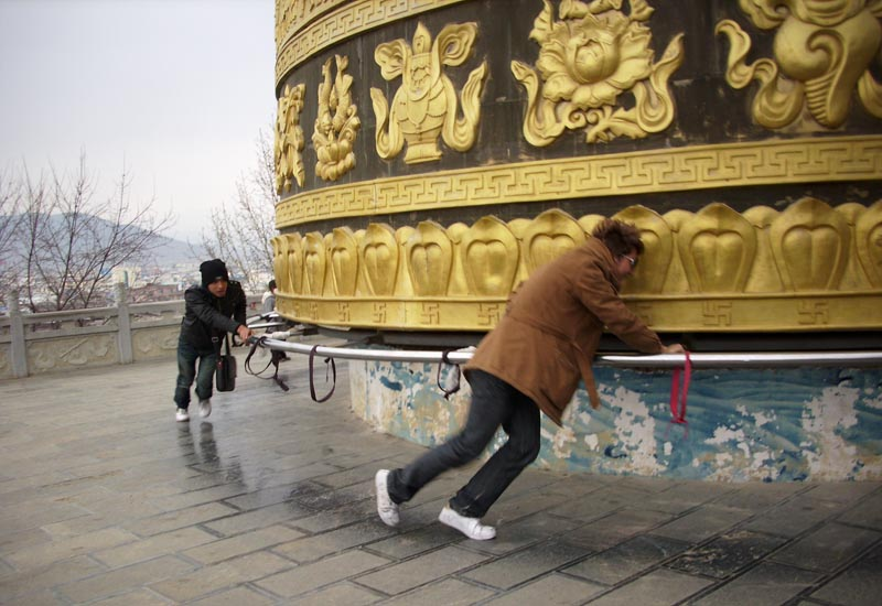 Young Tibetans  spinning a big prayer wheel for good luck, Shangri La, eastern Tibet,  March 2010. Photo: TPI/Mike Taylor