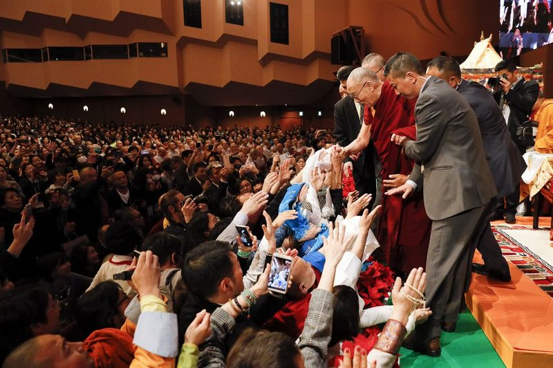 His Holiness the Dalai Lama shaking hands of members of the audience as he leaves the stage of the Pacifico Yokohama National Convention Hall at the conclusion of his teachings in Yokohama, Japan on November 15, 2018. Photo by Tenzin JIgme
