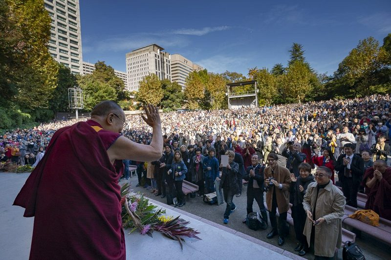 "His Holiness the Dalai Lama waving to the crowd as he arrives on stage at the Hibiya Open-Air Concert Hall for his public talk on ""One - We are One Family"" in Tokyo, Japan on November 17, 2018. Photo by Tenzin Choejor"