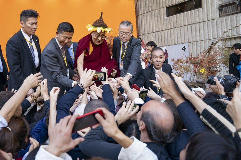 His Holiness the Dalai Lama reaching out to touch the hands of members of the audience at the conclusion of his talk at the Hibiya Open Air Concert Hall in Tokyo, Japan on November 17, 2018. Photo by Tenzin Choejor